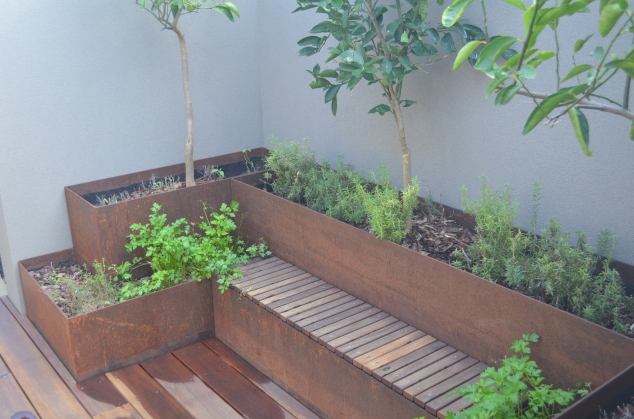 Herbs planted outside the kitchen.  (I love the rusty look, but does it mean iron fortified herbs?)
