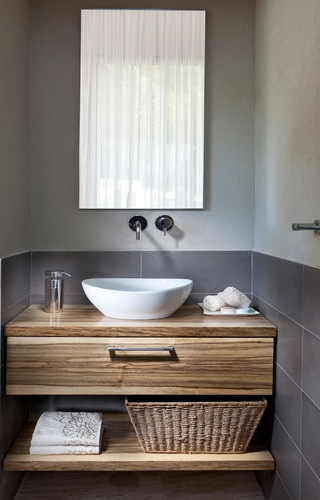 A little darker grey and the wood seem to make this powder room a bit masculine.