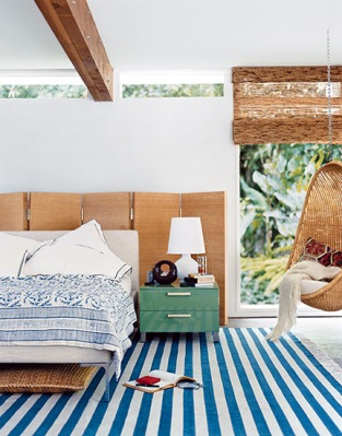 """Wooden divider provides a """"wall"""" behind the bed."""