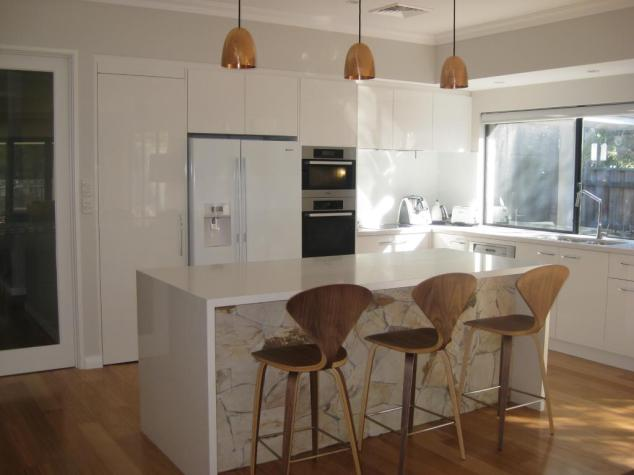 Caesarstone , under bench stone by   ,  Stanley hammered copper pendants from Dunlin,  stools.